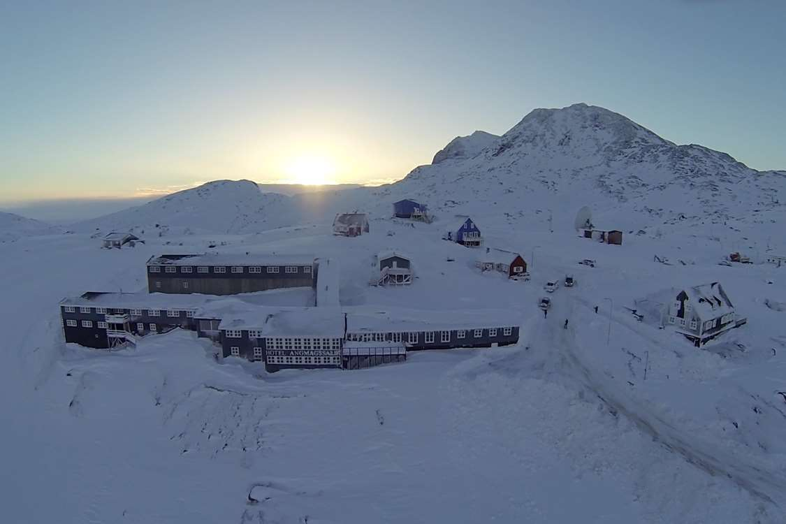 Aerial view of the hotel with sunrise in background in Winter. Photo by Hotel Angmagssalik