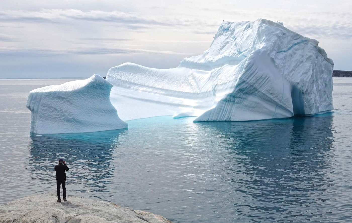 Man looking at a large iceberg near Disko Bay. Photo by Espen Andersen, Visit Greenland