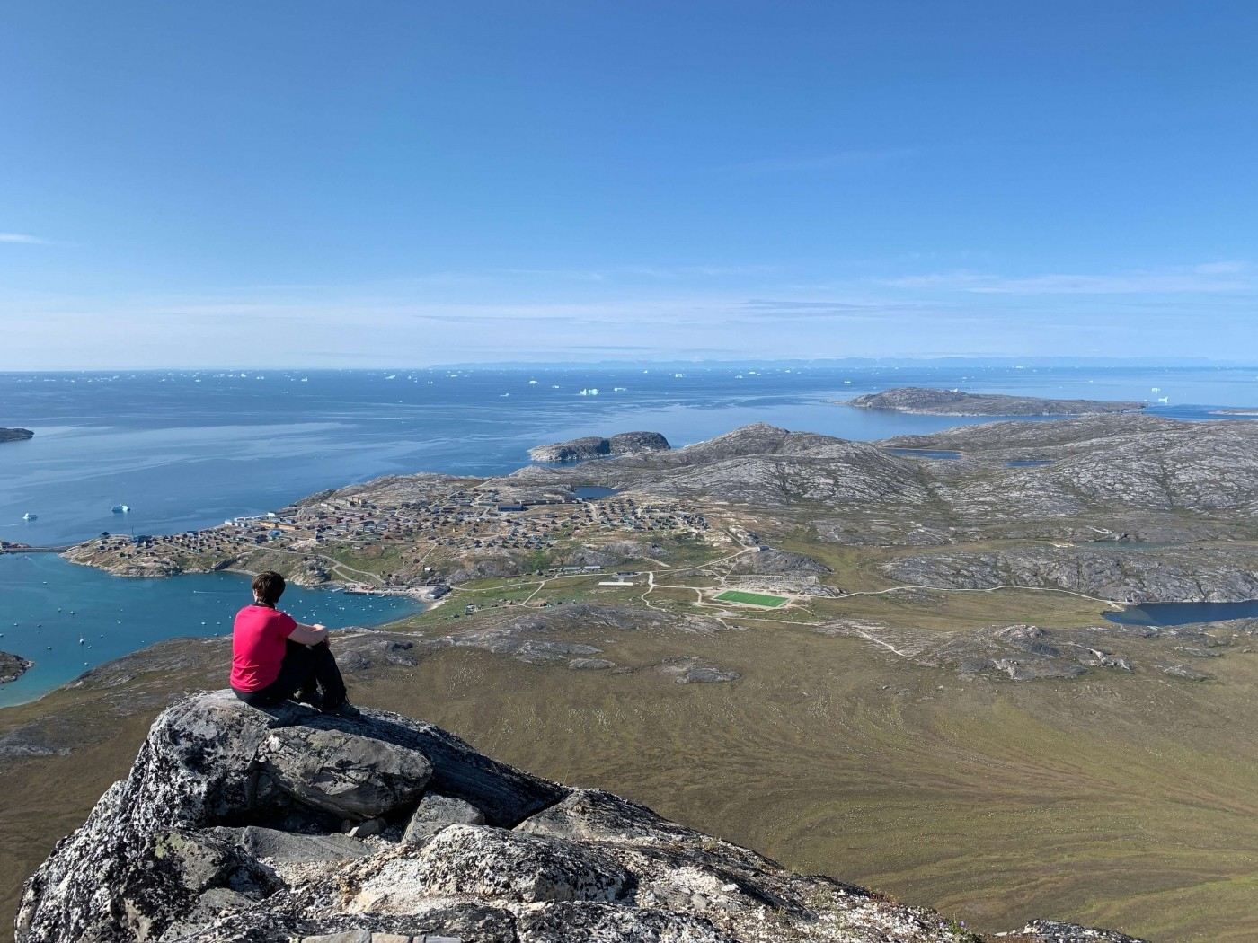 Hiker sitting on a rock and enjoying the view over Disko Bay. Photo by Espen Andersen, Visit Greenland