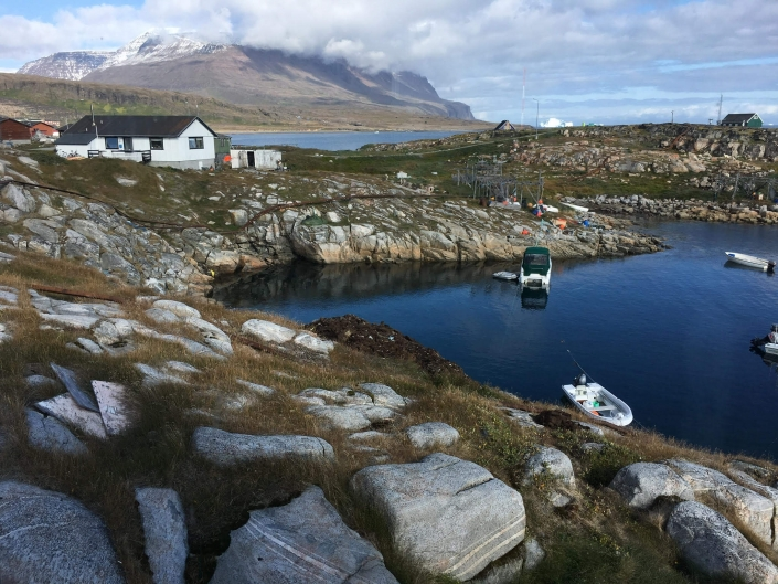 View over a little harbour in Qeqertarsuaq with large mountains in the background. Photo by Skansen – Your Home, Visit Greenland