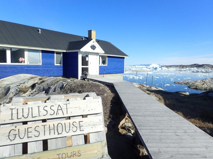 Frontside view of Blue House with Ilulissat Icefjord in background. Photo by Ilulissat Guesthouse - Visit Greenland