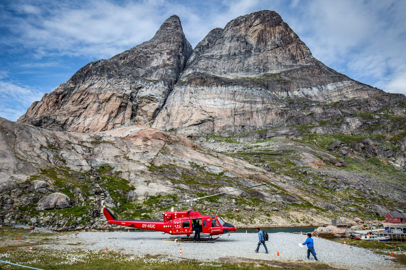 Passengers and service personel approaching a parked Air Greenland Bell 212 helicopter in Aappilattoq in South Greenland. Photo by Mads Pihl.