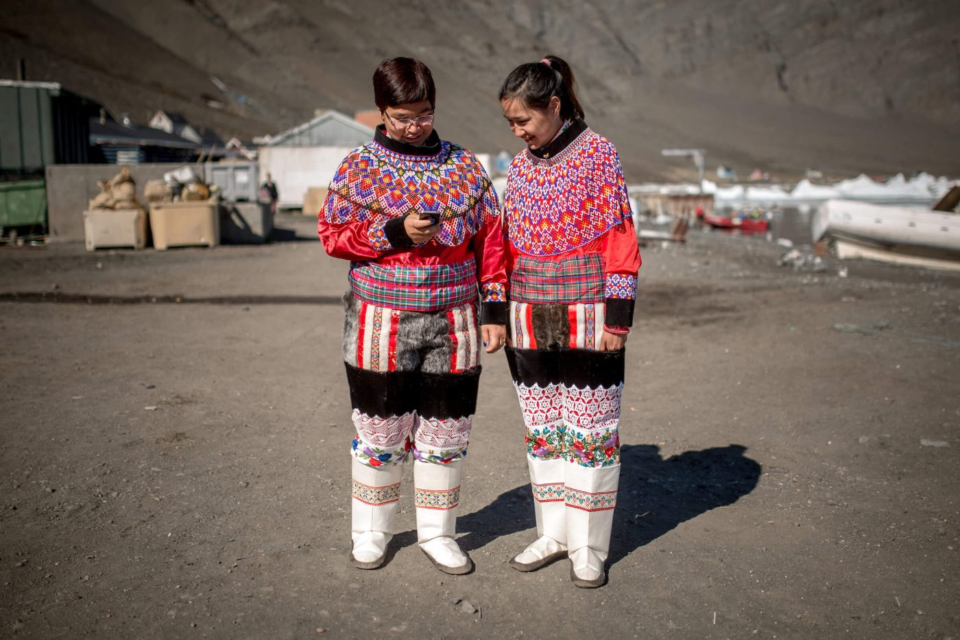 Two girls from Illorsuit in Greenland on the smart phone while wearing national costumes. Photo by Mads Pihl.