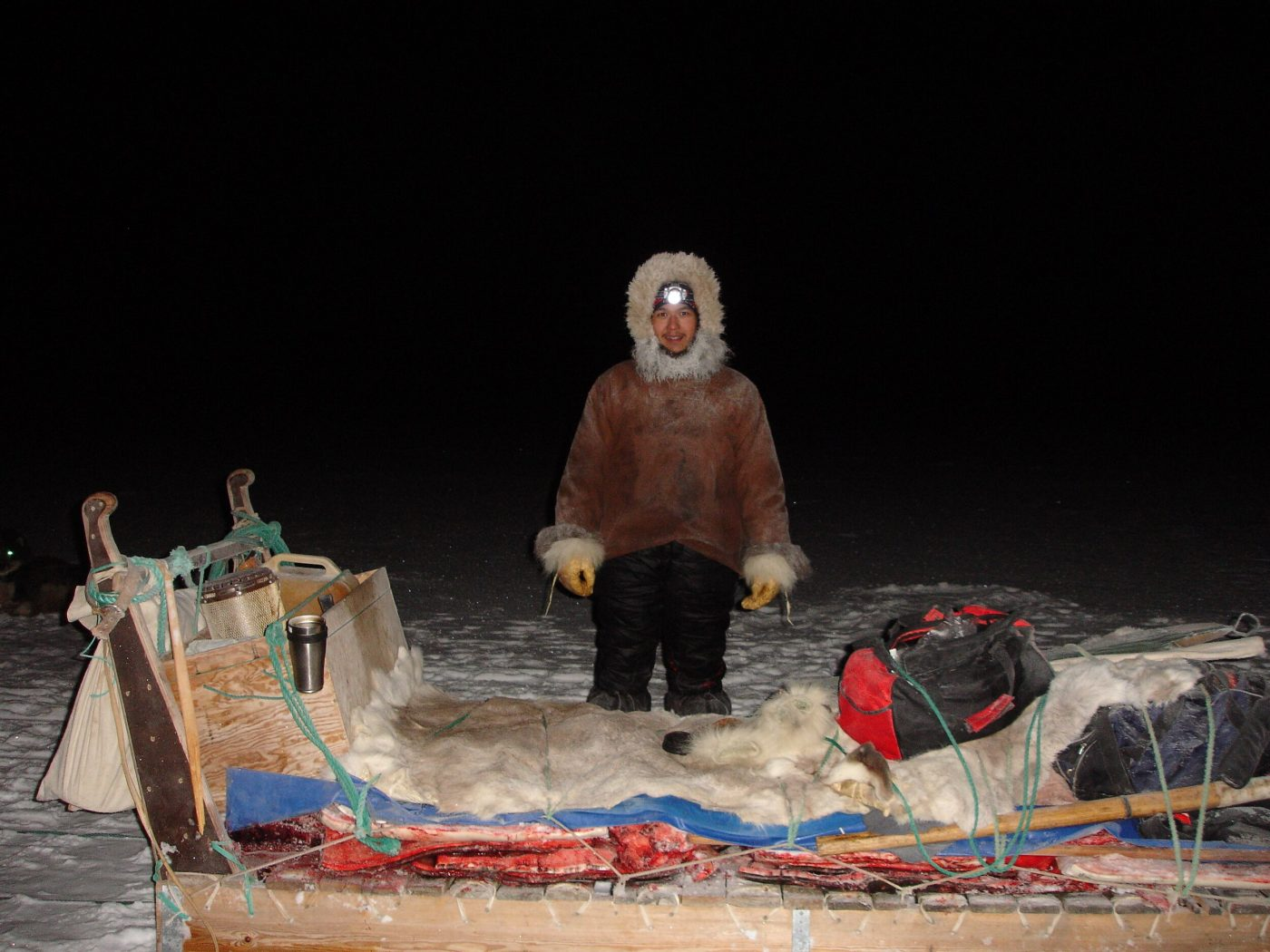 Happy hunter in fur anorak with catch of the day attached to his sleigh in Qaanaaq, North Greenland. Photo by Nunataq Atsuk Travel