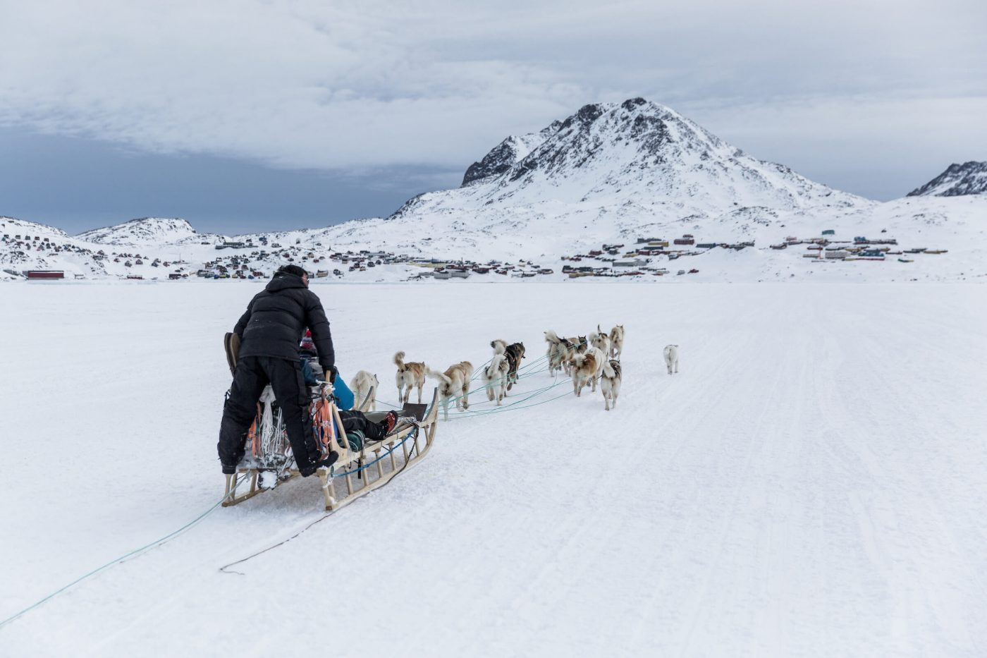 A dog sled approaching Tasiilaq in East Greenland over the sea ice. Photo by Mads Pihl - Visit Greenland