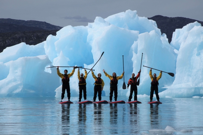 A group of stand up paddleboarders standing in front of iceberg. Photo by Nuuk Adventure - Visit Greenland