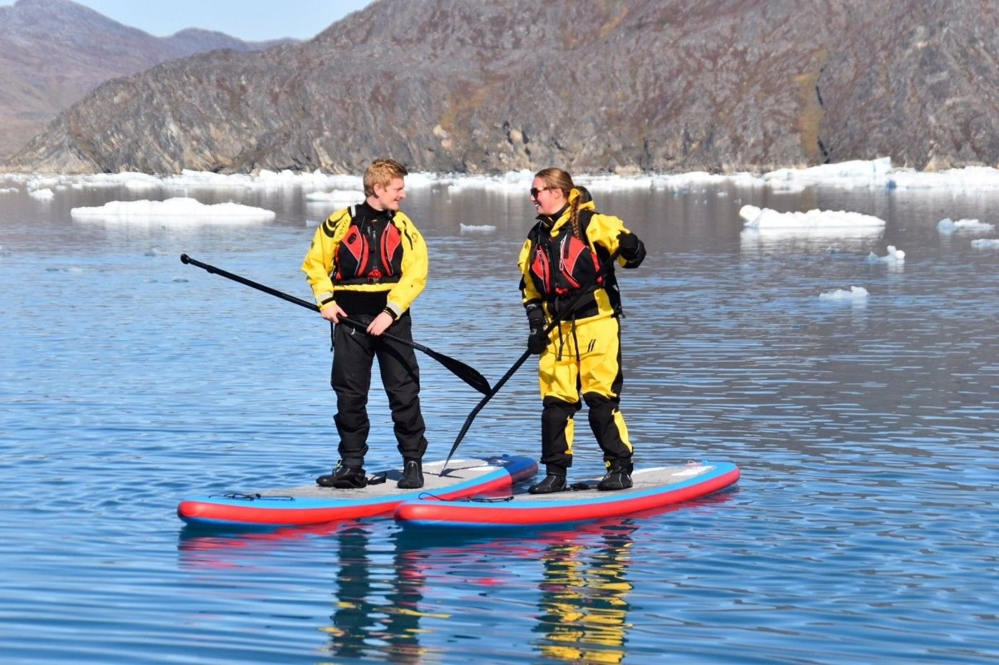 Couple stand up paddleboarding in Summer. Photo by Nuuk Adventure - Visit Greenland