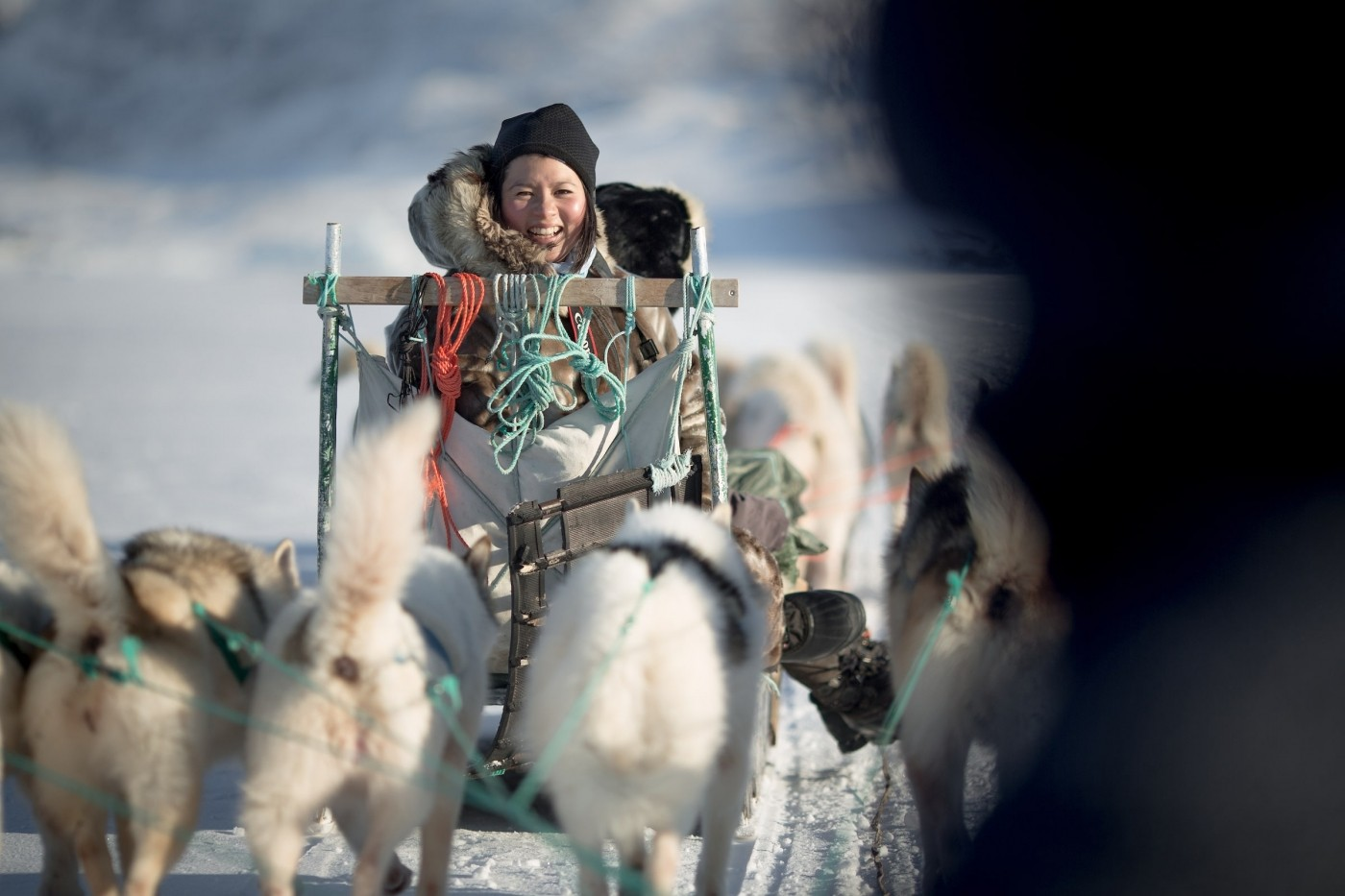 A Chinese traveler looking back at a following dog sled near Ilulissat in Greenland. Photo by Mads Pihl - Visit Greenland