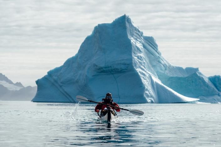A kayaker paddles with a large iceberg directly behind him, Just North Of Kuummiut. Photo by Chris Brin Lee Jr. - Visit Greenland