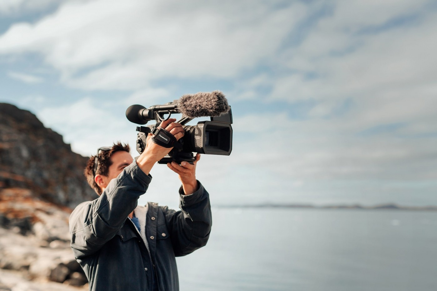 Behind the scenes shot of videographer Aningaaq Rosing Carlsen filming the fjord in Nuuk in Greenland. Photo by Rebecca Gustafsson - Visit Greenland