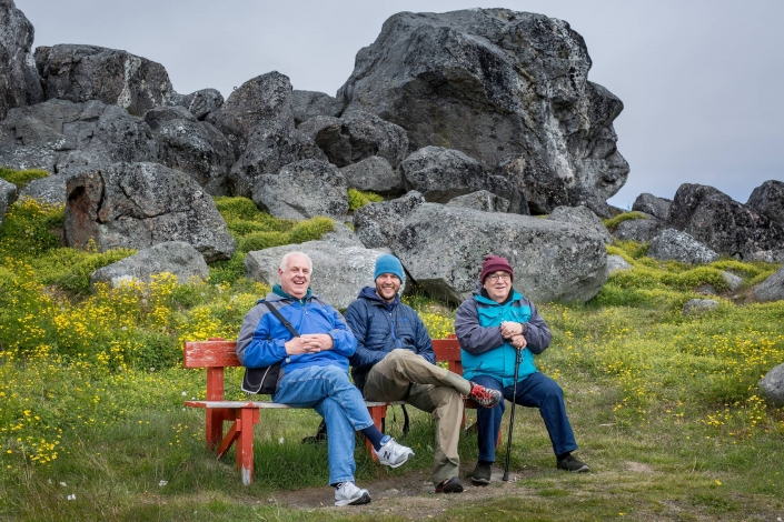 Cruise guests on a bench in front of the Knud Rasmussen rock in Nanortalik in South Greenland. Photo by Mads Pihl - Visit Greenland