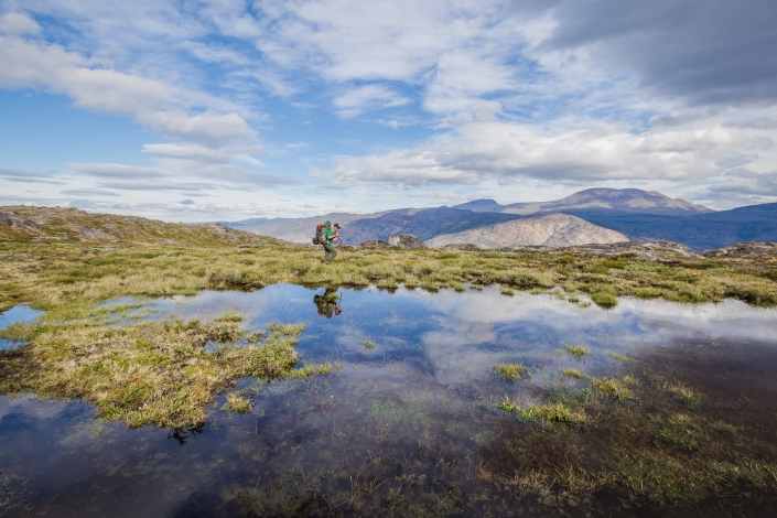 Hiker navigates a bog marsh along the Arctic Circle Trail. Photo by Lina Stock - Visit Greenland