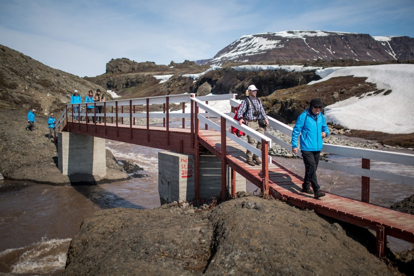 Hikers on the trail to the basaltic rocks in Qeqertarsuaq in Greenland. By Mads Pihl