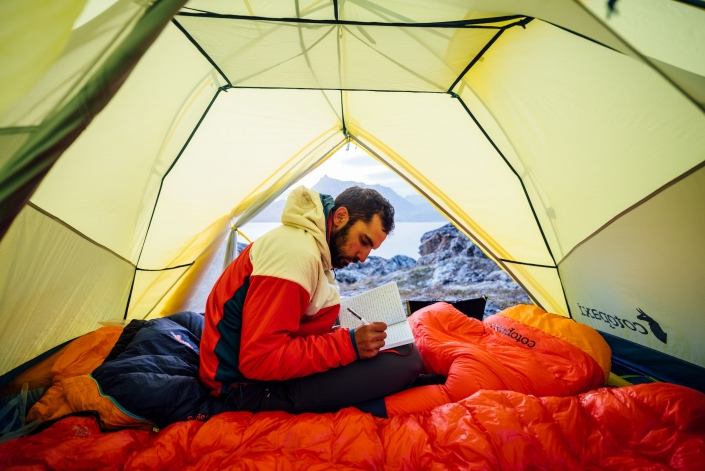 Inside a tent, a camper journals to his wife, water background, Between Kulusuk & Kuummiut. Photo by Chris Brin Lee Jr. - Visit Greenland