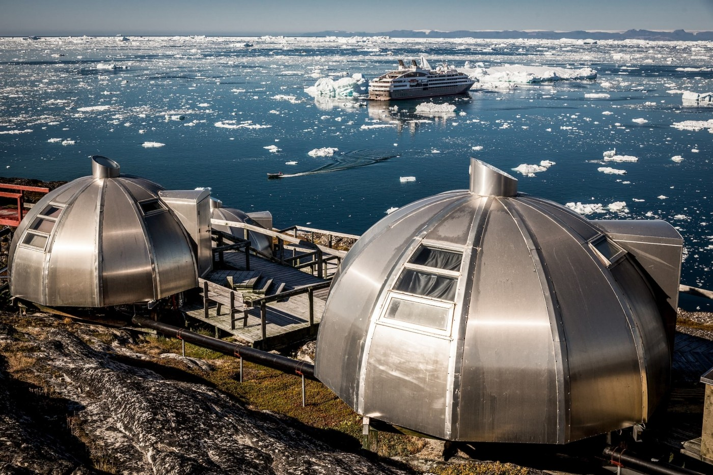 Ponant Cruises' L'Austral in front of the Hotel Arctic igloos in Ilulissat in Greenland. By Mads Pihl