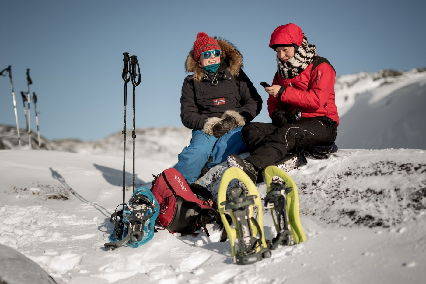 Two snowshoers taking a break to update their lives on social media near Iluissat in Greenland. Photo by Mads Pihl - Visit Greenland
