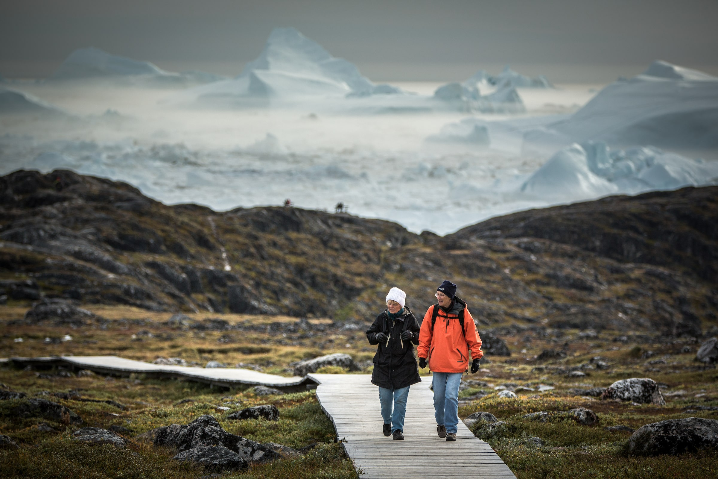 Two women on the boardwalk near Sermermiut with icebergs in the background in Ilulissat in Greenland. Photo by Mads Pihl