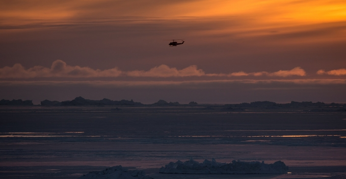 A Bell 212 Air Greenland helicopter over the Disko Bay in the sunset. Photo by Mads Pihl - Visit Greenland