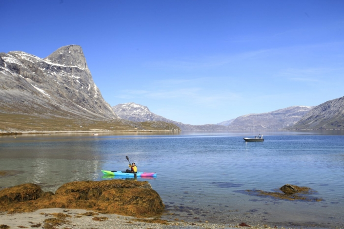 A woman kayaking in Nuuk Fjord with a small boat behind her. Photo by Greenland Waterways - Visit Greenland