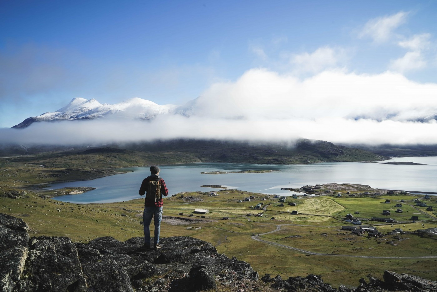 Hiker standing on rock looking at the settlement in front of him in South Greenland. Photo by Guide to Greenland