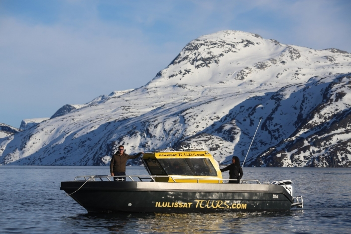 Ilulissattours boat sailing in front of mountain covered in snow in Winter. Photo by Ilulissat Tours - Visit Greenland