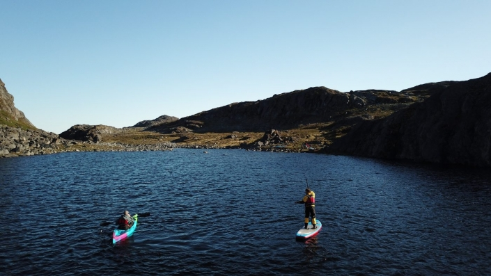One person kayaking while another person is stand up paddling around Nuuk area. Photo by Greenland Waterways - Visit Greenland