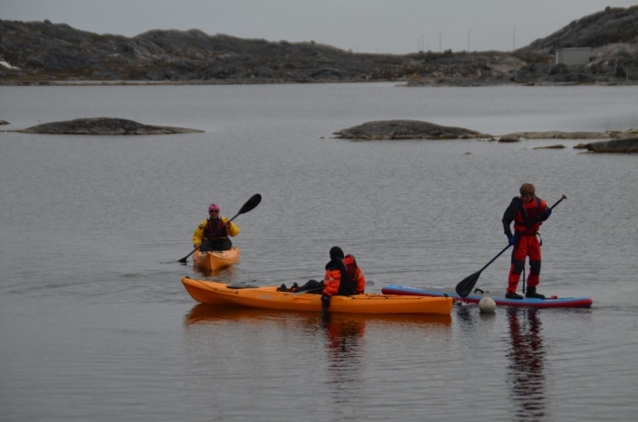 Two people kayaking while another person is stand up paddling around Nuuk area. Photo by Greenland Waterways - Visit Greenland