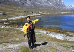 Woman in survival suit and lifevest at the shore. Photo by Greenland Waterways - Visit Greenland
