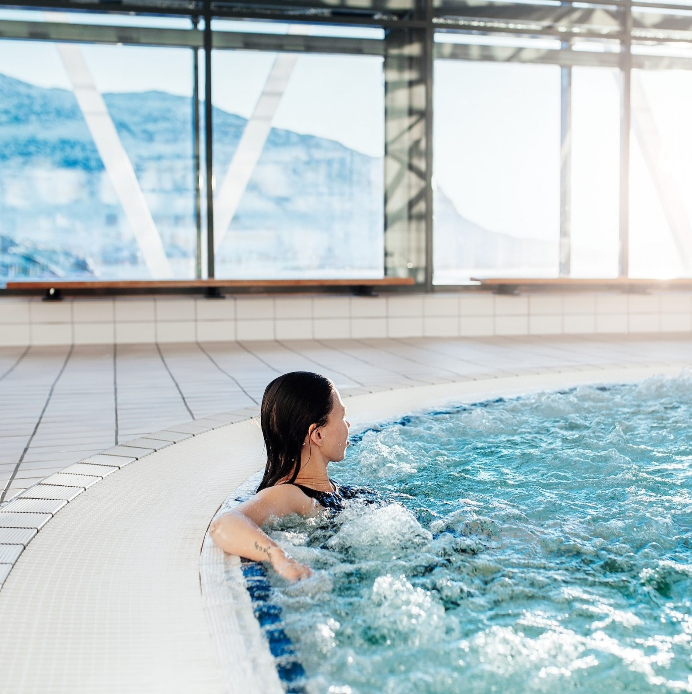 Woman relaxing in the bubble bath in the indoor swimming pool Malik in Nuuk in Greenland. Photo by Rebecca Gustafsson - Visit Greenland