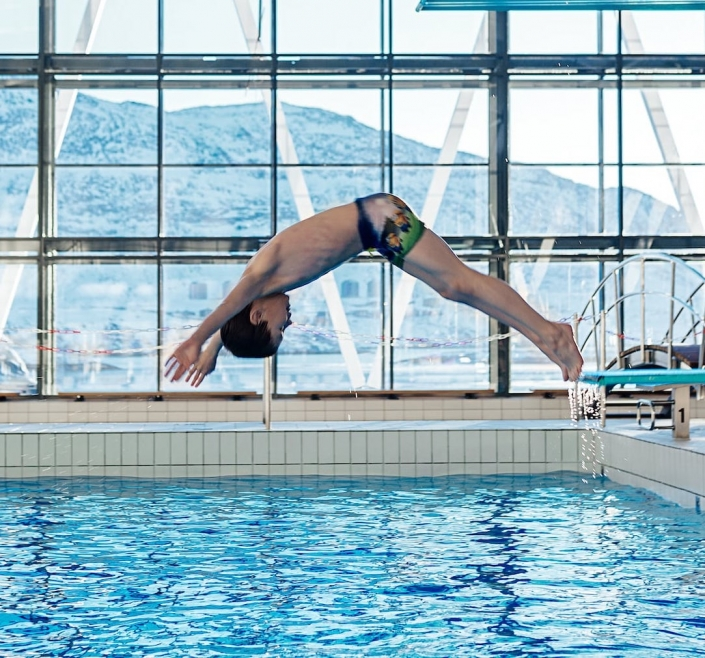 Young boy diving from the lowest trampoline in the indoor swimming pool Malik in Nuuk in Greenland. Photo by Rebecca Gustafsson - Visit Greenland
