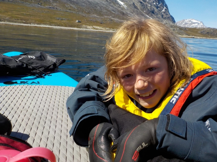 Young boy smiling at camera while holding on to a stand up paddle in the water. Photo by Greenland Waterways - Visit Greenland