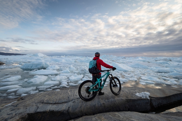 Chris Winter enjoying one of the most spectacular views you can get to by mountain bike. Ilulissat Icefjord, Ilulissat, North Greenland. Photo by Ben Haggar - Visit Greenland