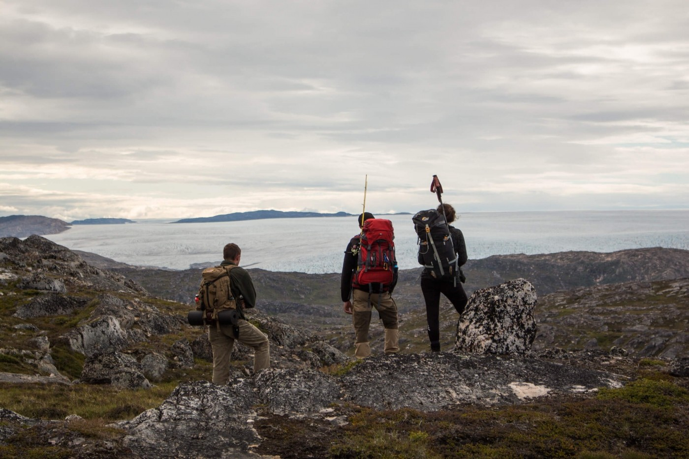 Hikers taking a break to observe the mountains and icesheet surrounding them.
