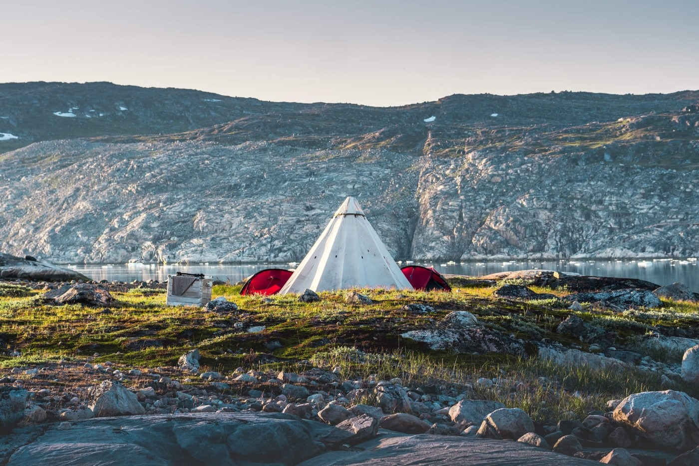 Camp setup near a mountain at the waterfront.