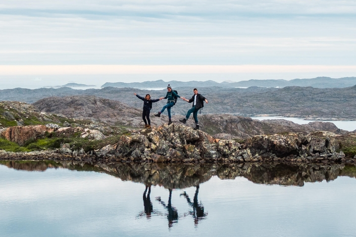 Three hikers having fun walking along the water.