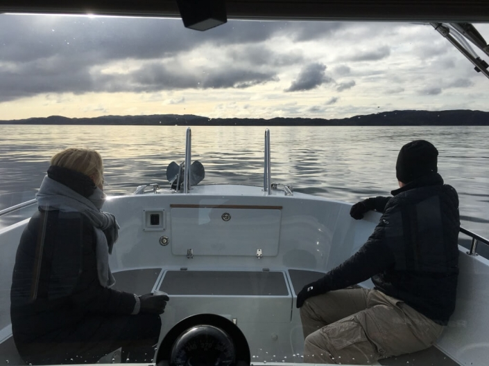 Two passengers sitting at the back of the charter boat enjoying the view. Photo by Qajaq Seaway