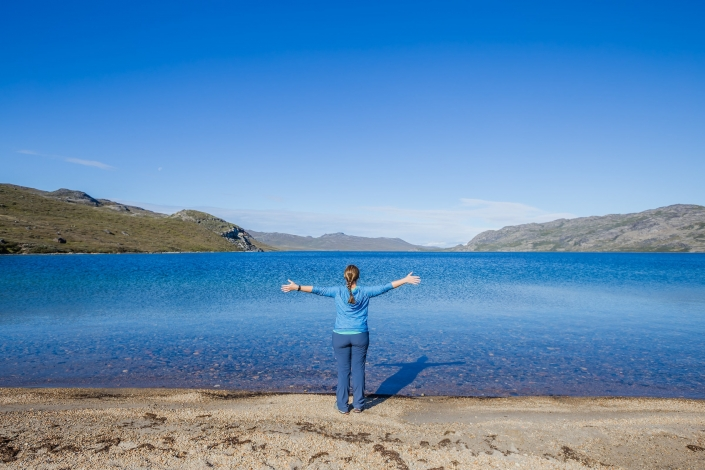 Female hiker enjoying the scenery at Amitsorsuaq Lake along the Arctic Circle Trail. Photo by Lina Stock - Visit Greenland