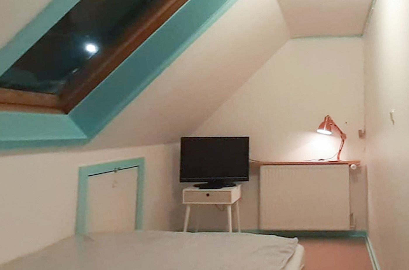 Bedroom under the roof with tv. Photo by Mikami Hostel