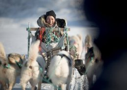 A Chinese traveler looking back at a following dog sled near Ilulissat in Greenland. Photo by Mads Pihl