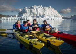A coffee break in front of an iceberg on a PGI Greenland kayak trip in Greenland. By Mads Pihl