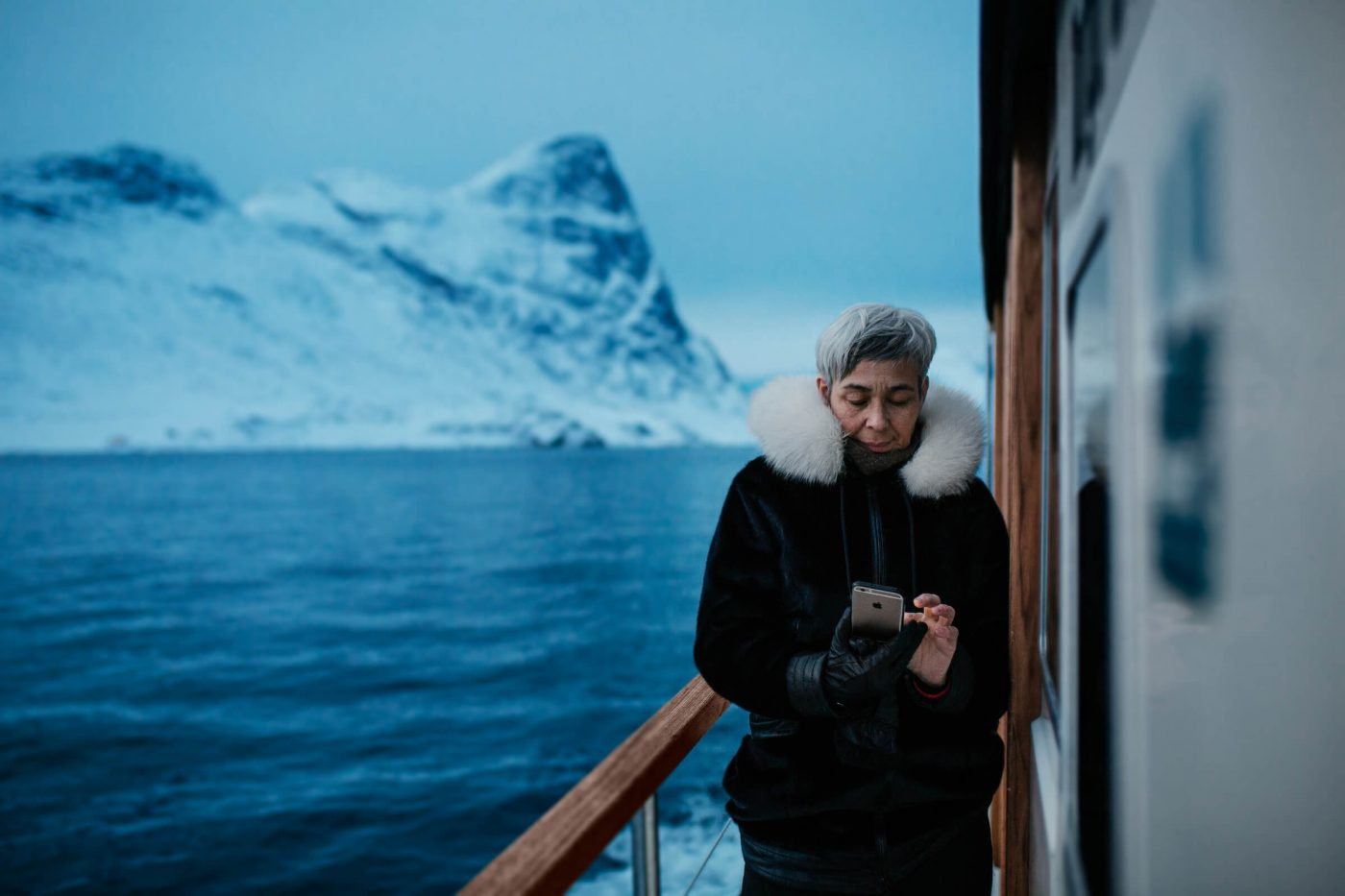 A greenlandic woman with her phone on a tour with Arctic Boat Charter near Nuuk in Greenland. Photo by Rebecca Gustafsson