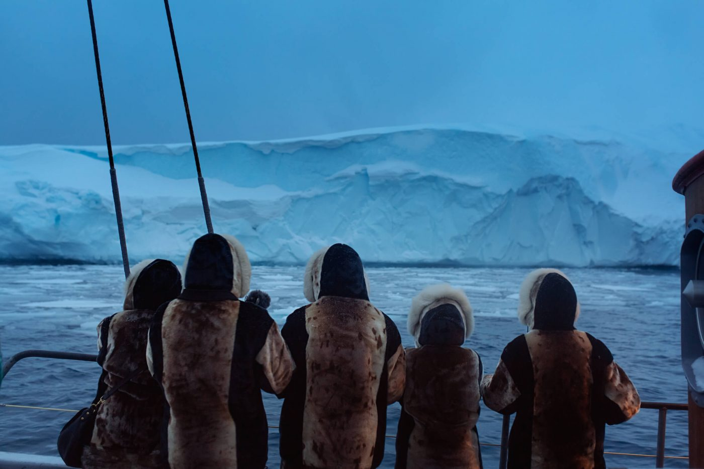 A group of seal skin dressed tourists enjoying the Ilulissat icefjord during blue hour in Greenland. By Rebecca Gustafsson
