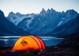 A lit tent at sunset looking north towards three peaks, Camp In Tasiilaq Fjord. By Chris Brinlee Jr