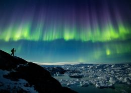 A photographer on a photo tour in North Greenland captures the perfect nighttime shot of northern lights, the starry night sky, and icebergs in the Ilulissat Icefjord. Photo by Paul Zizka