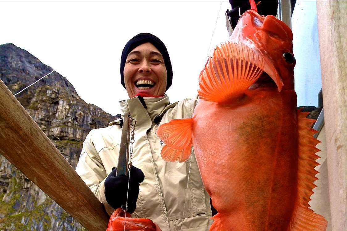 A happy guest with a red fish on an ABC Charter boat tour. Visit Greenland