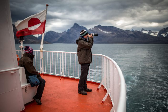 A photographer on the upper deck of Sarfaq Ittuk in Greenland. Visit Greenland