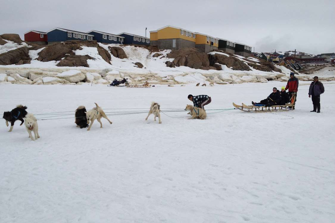 People on a dog sled leaving from Kulusuk, going to Apusiajik ('Little' glacier). Photo by Arctic Wonderland Tours, Visit Greenland