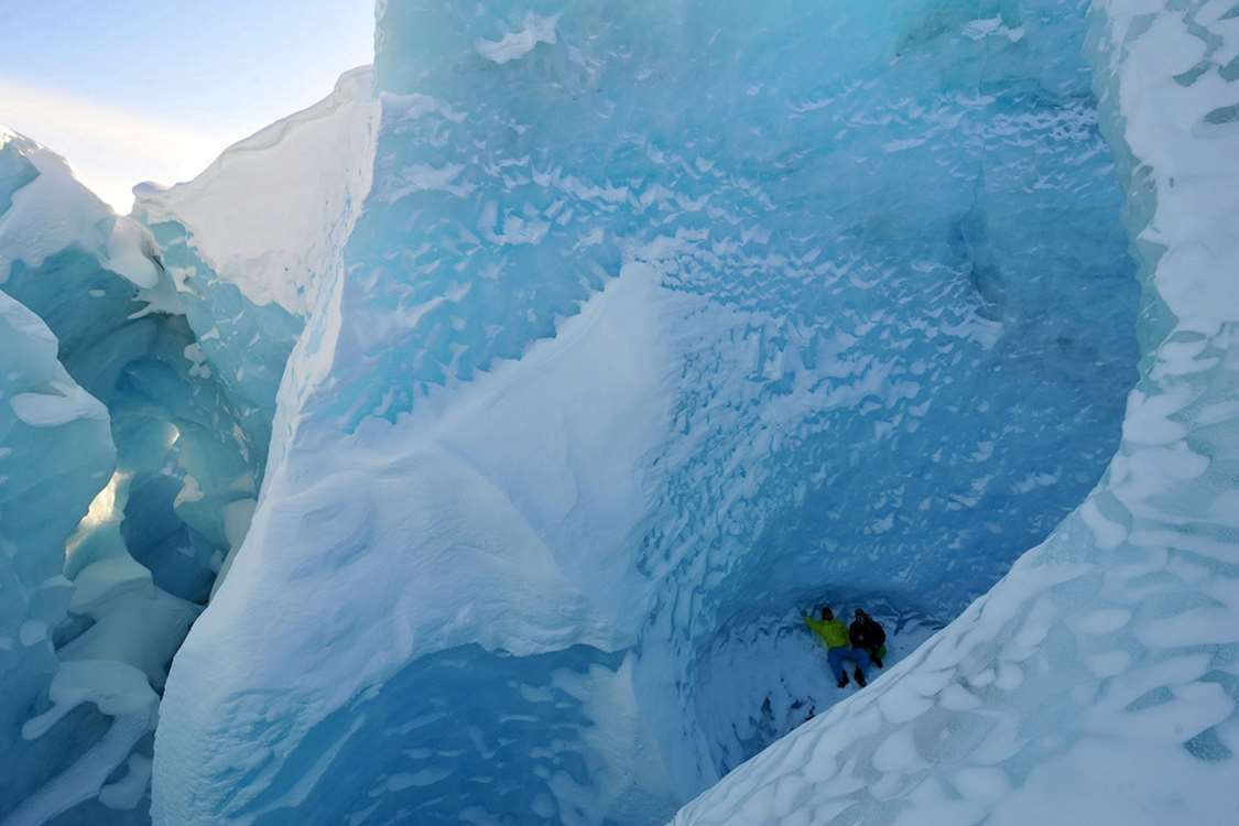 Two hikers taking a break inside a glacier. Photo by Arctic Wonderland Tours, Visit Greenland