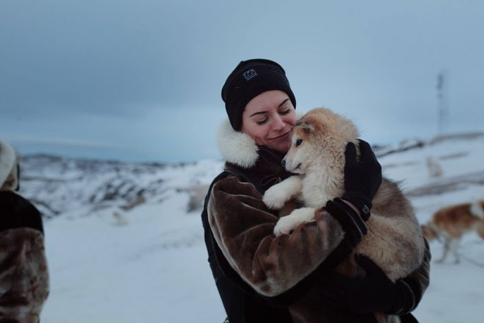 Australian social media influencer Sorelle Amore holding a greenlandic sled dog puppy in Ilulissat in Greenland. Photo by Rebecca Gustafsson