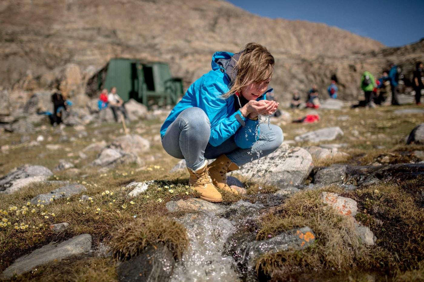 Drinking fresh water from a stream near Uummannaq in Greenland. By Mads Pihl